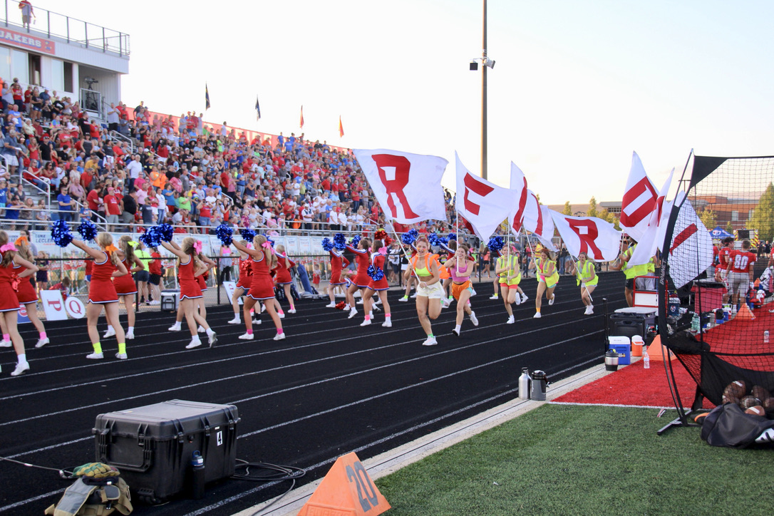 Students parade the Red Pride flags after the Quakers score a Homecoming touchdown
