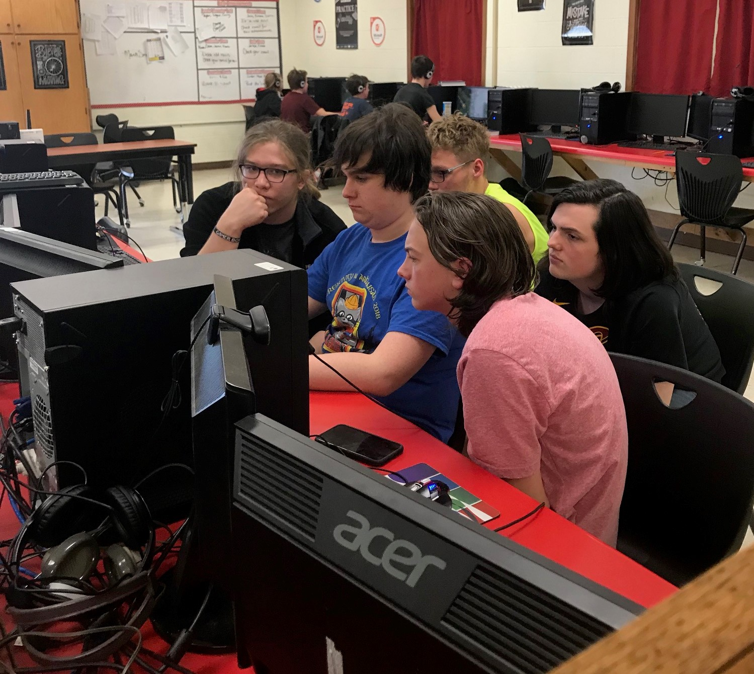 Photo of the members of a club crowded around a computer