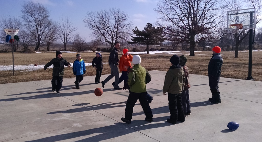 photo of students playing basketball outside