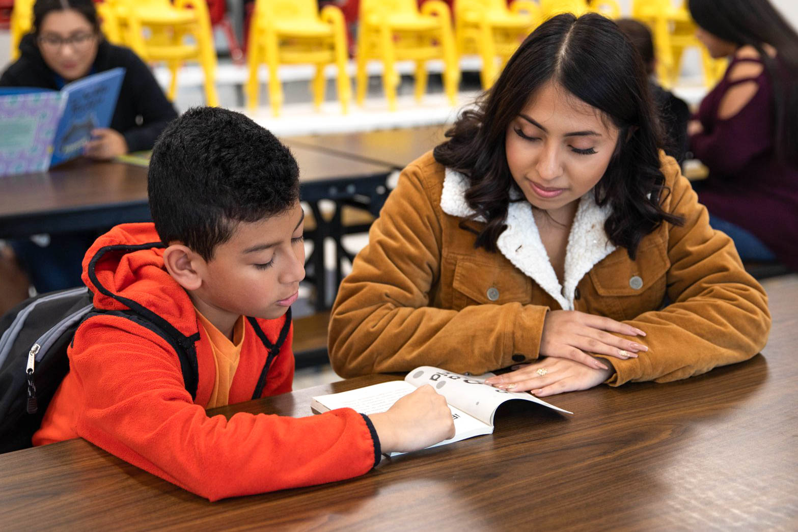 Photo of a teacher with a student reading.
