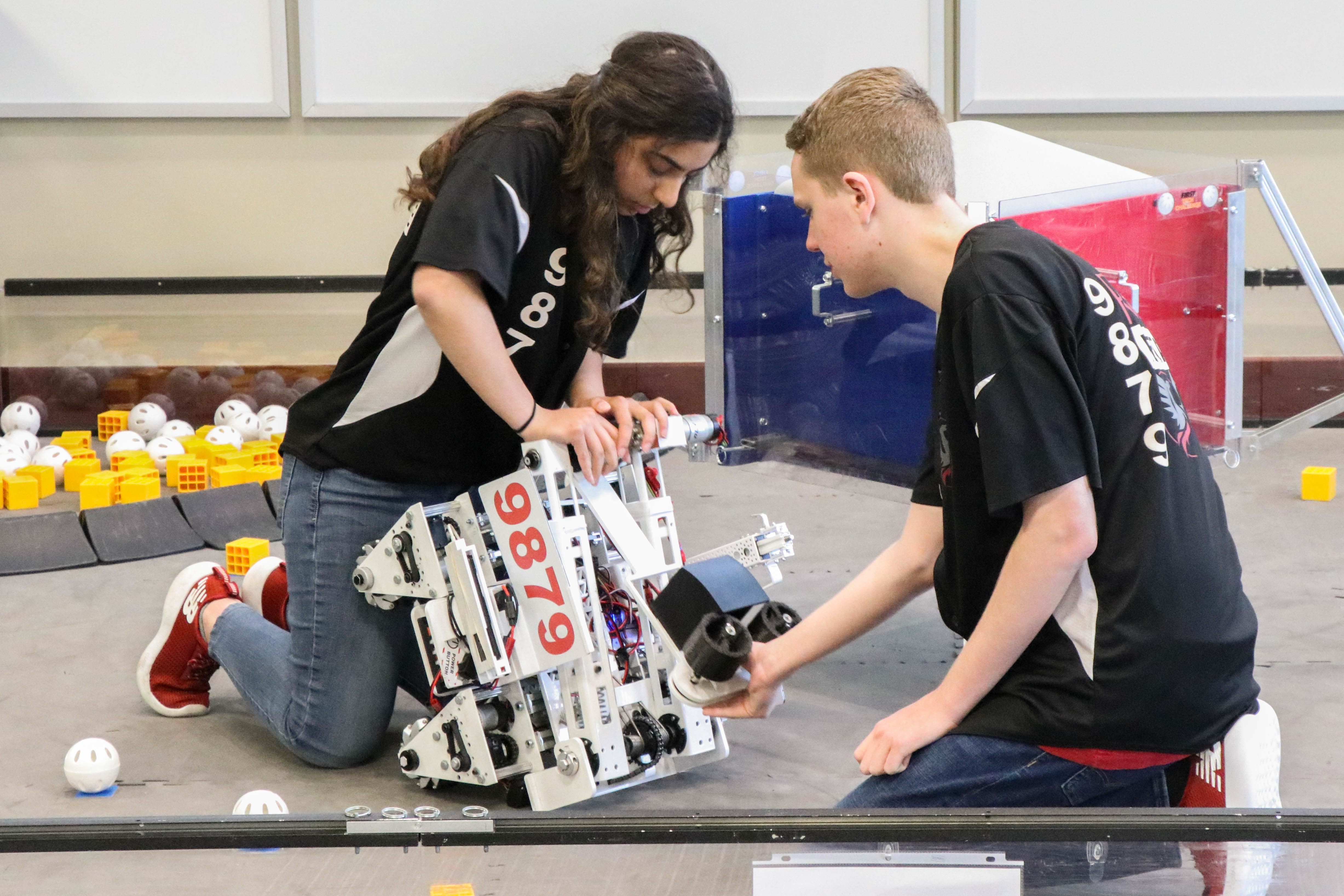 Photo of two students with a robot.