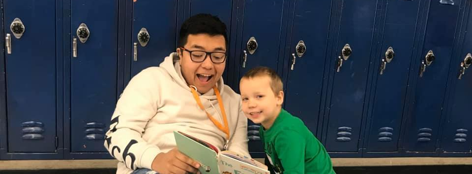 A teacher and  a student reading together.