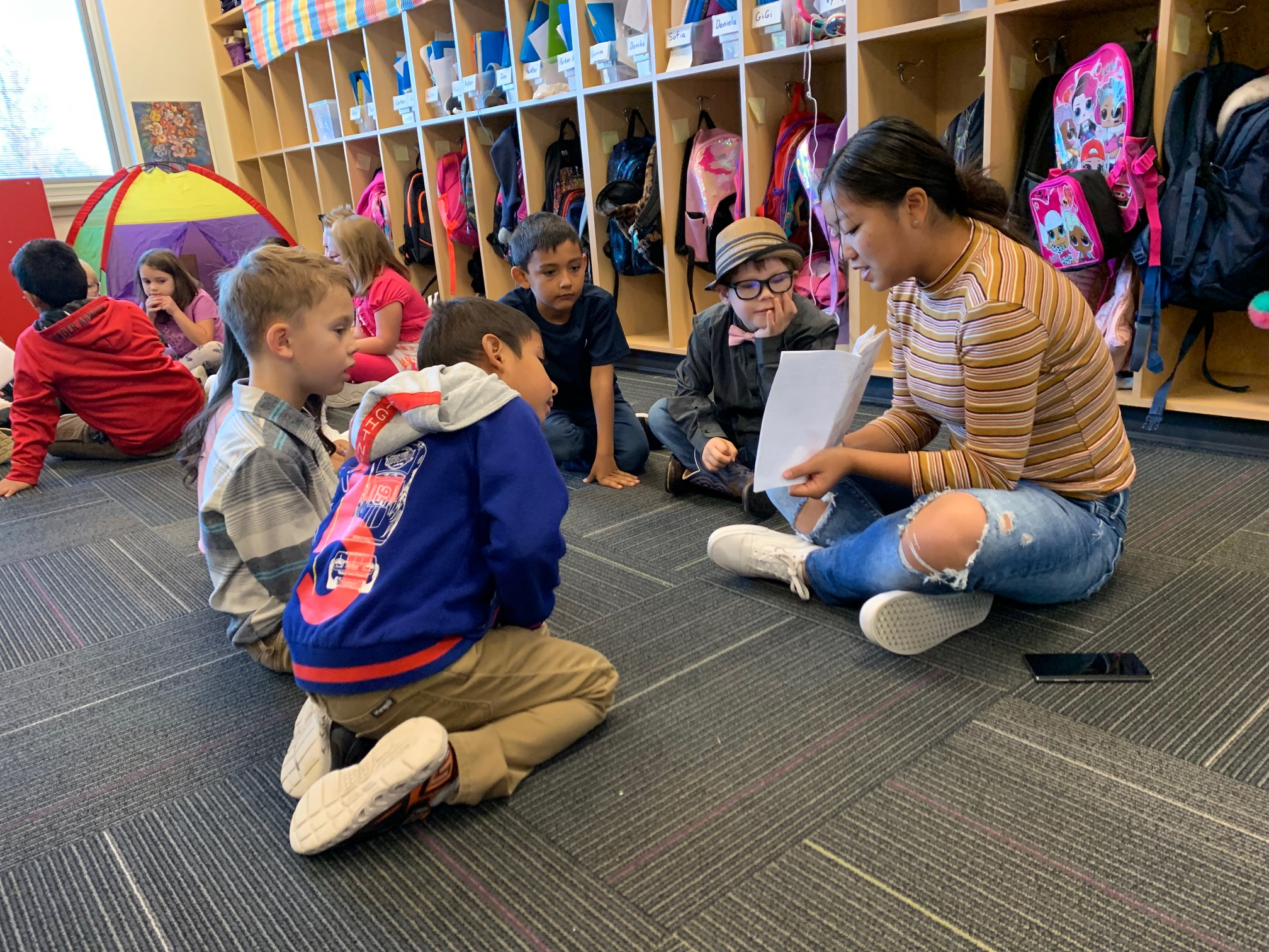 A photo of students being read to by a teacher