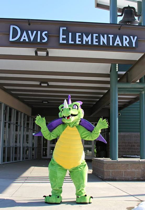 A photo of the Davis mascot in front of the school building