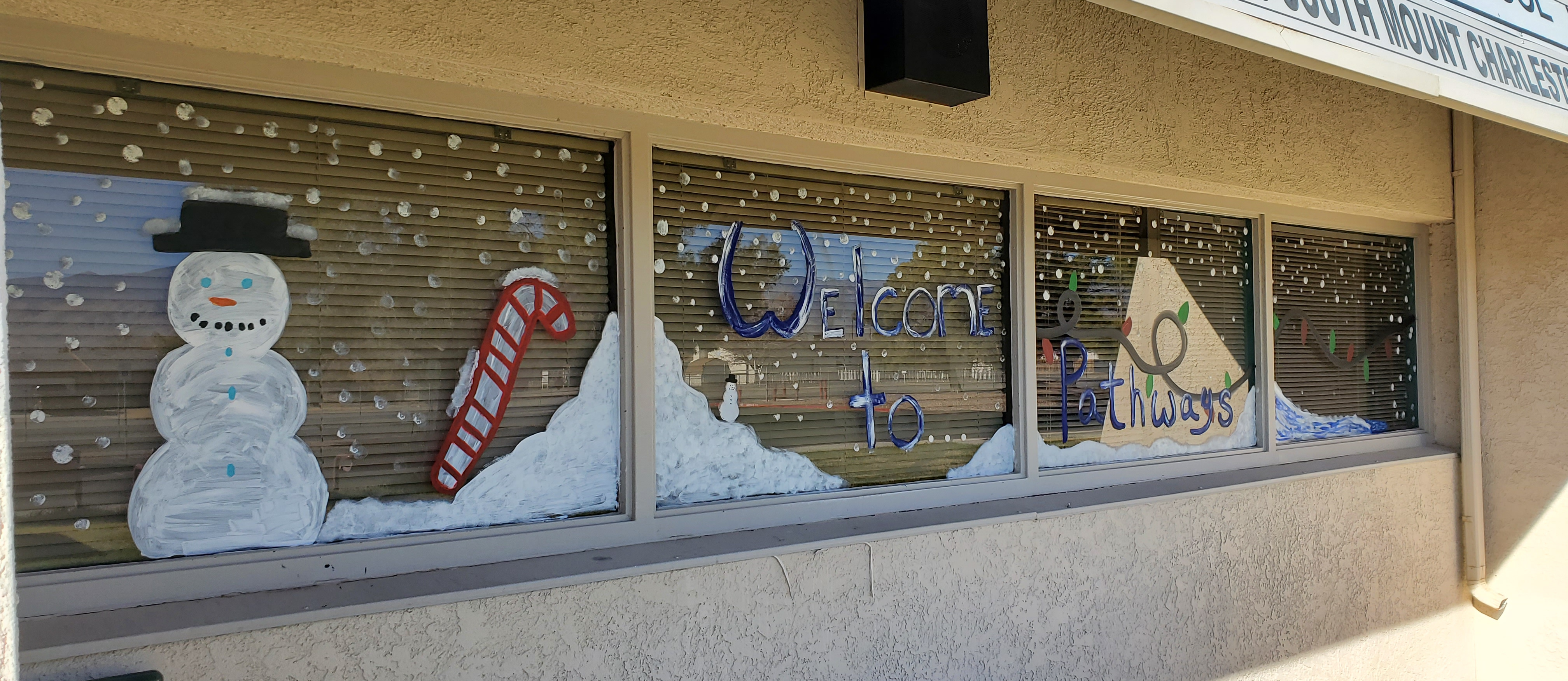 Window front with winter motifs. Drifted snow banks, a snow man, a candy cane, and the the words 'welcome to pathways' in blue script