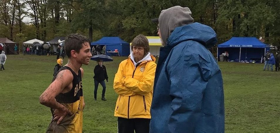 A runner with Craig Sluga, Head Coach & Karen Barringer, Assistant Coach