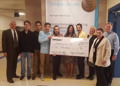 A photo of students and teachers holding a giant check from Verizon