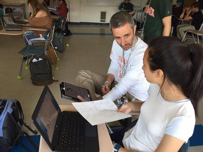 A photo of a teacher helping a student