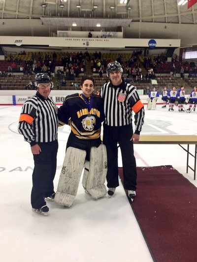 A photo of a hockey player with 2 refs