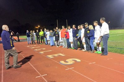 A photo of students and parents on the sidelines at a football game