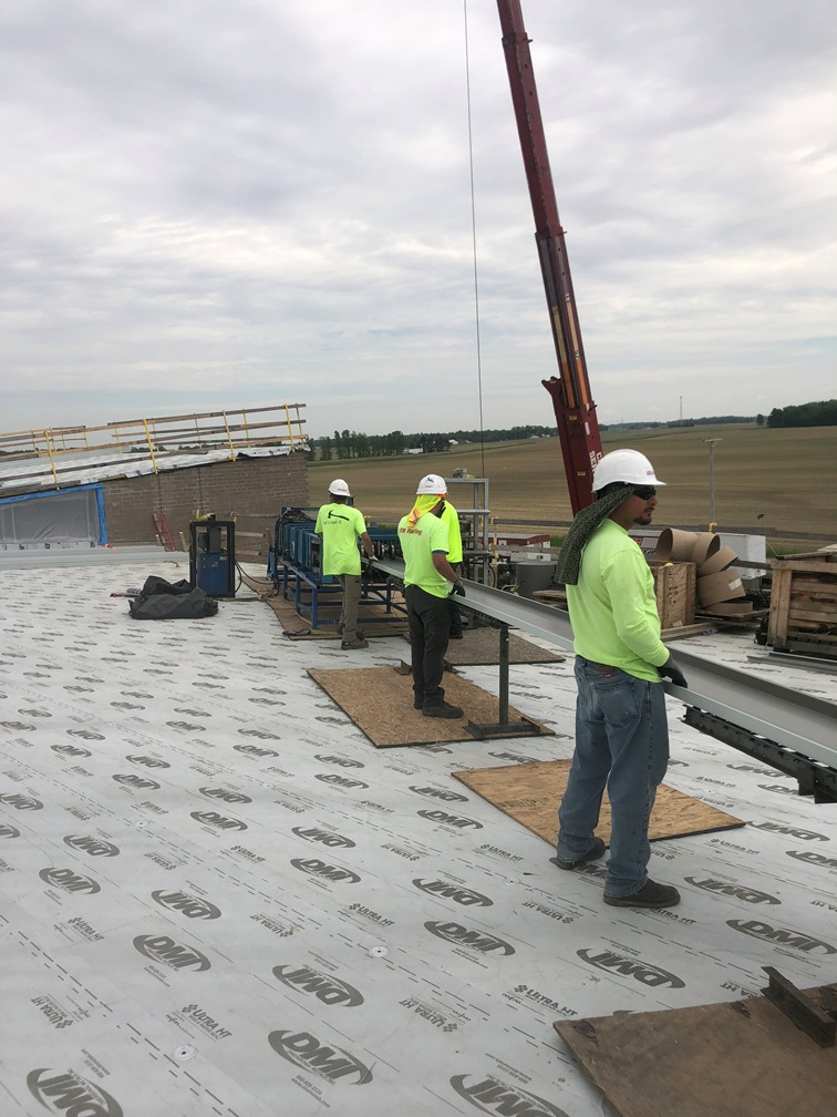 Photo of the Workers holding the roof metal so it does not bend.