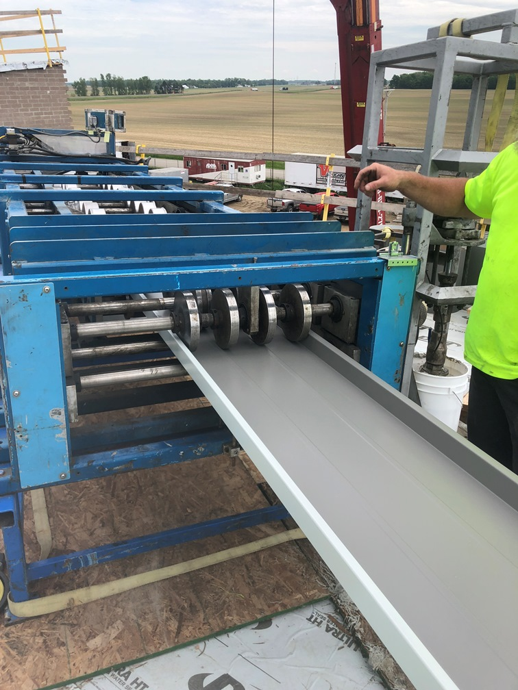 Photo of the Roof metal being formed on a machine on the roof.