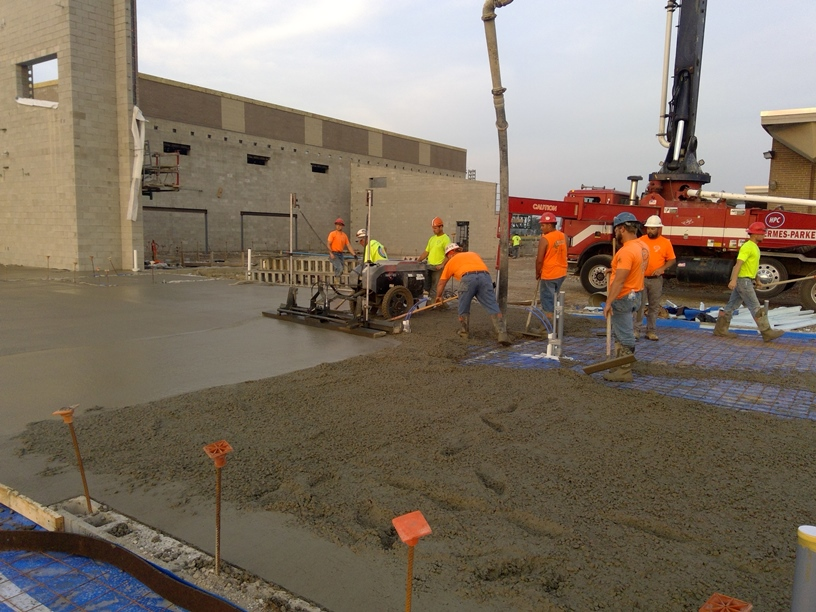 Photo of the workers pouring concrete in the new academic wing.
