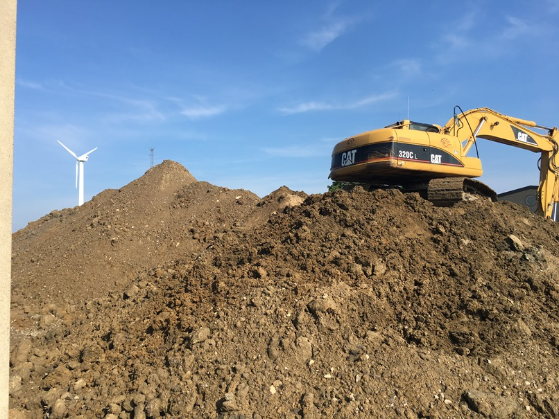 Photo of the mound of dirt next to the high school building is being moved to the back of the elementary school.