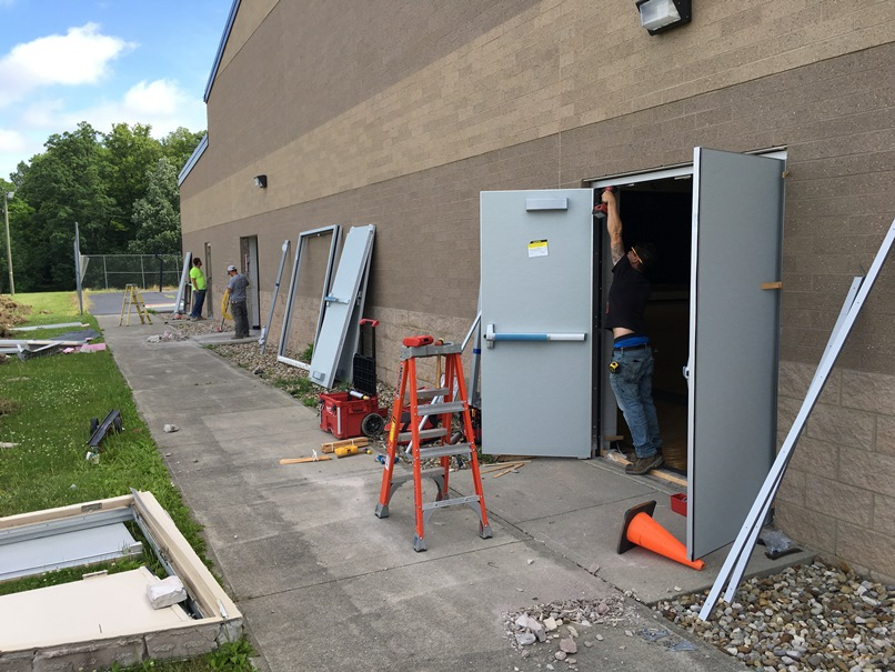 Photo of the Installation of new exterior doors at the back of the elementary school gym.