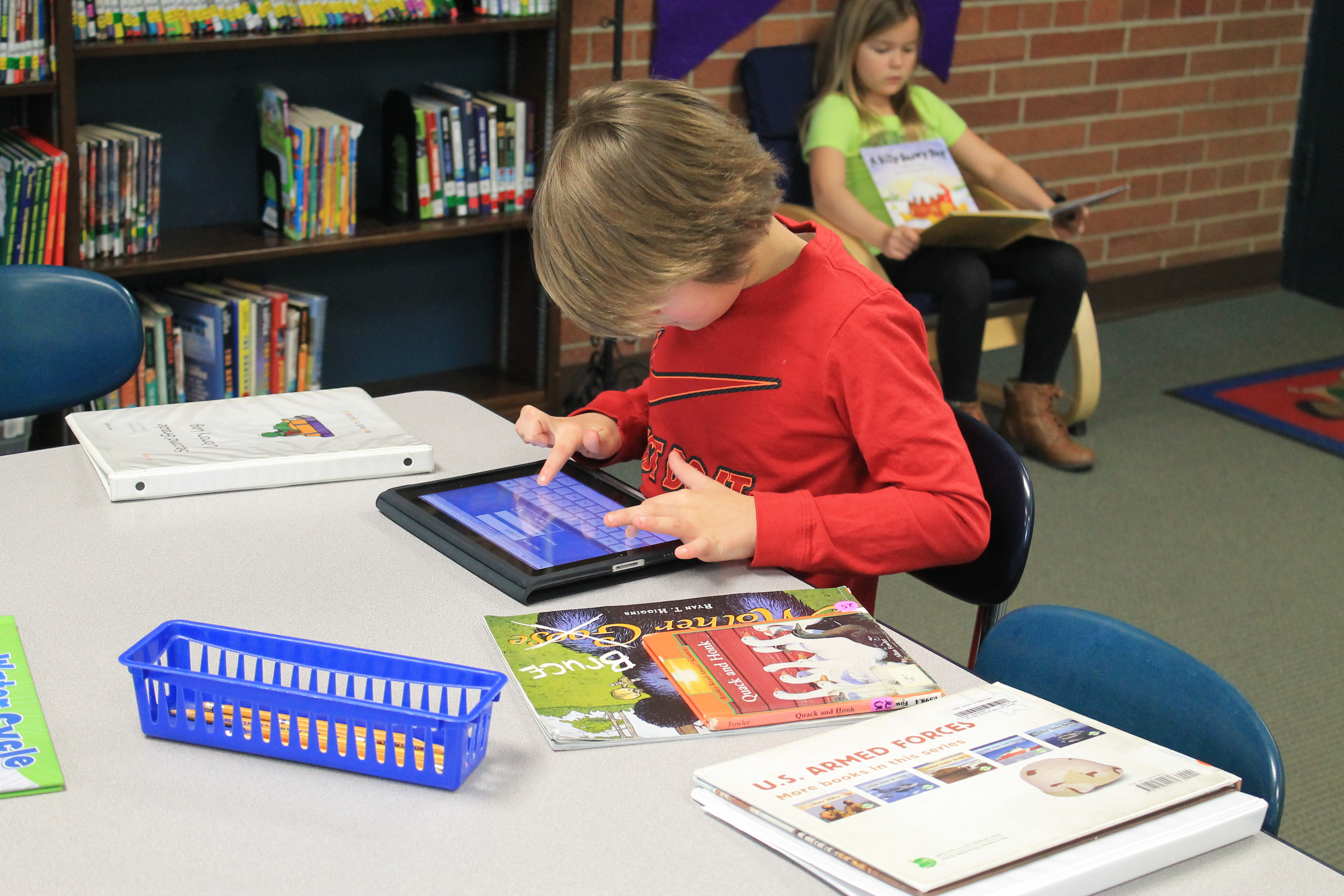 A small boy playing with an educational I-Pad in the library's school.