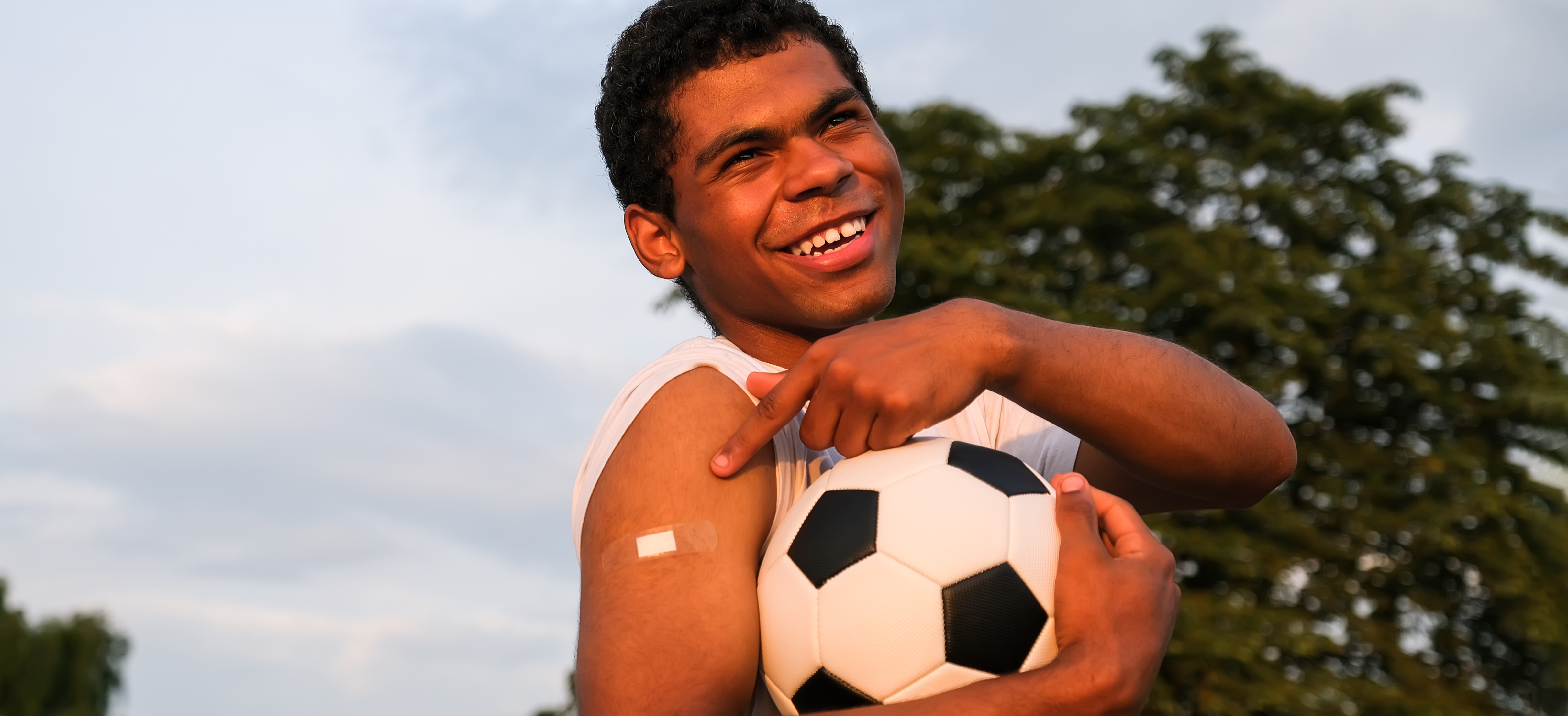 Vaccinated teenage boy smiling holding soccer ball