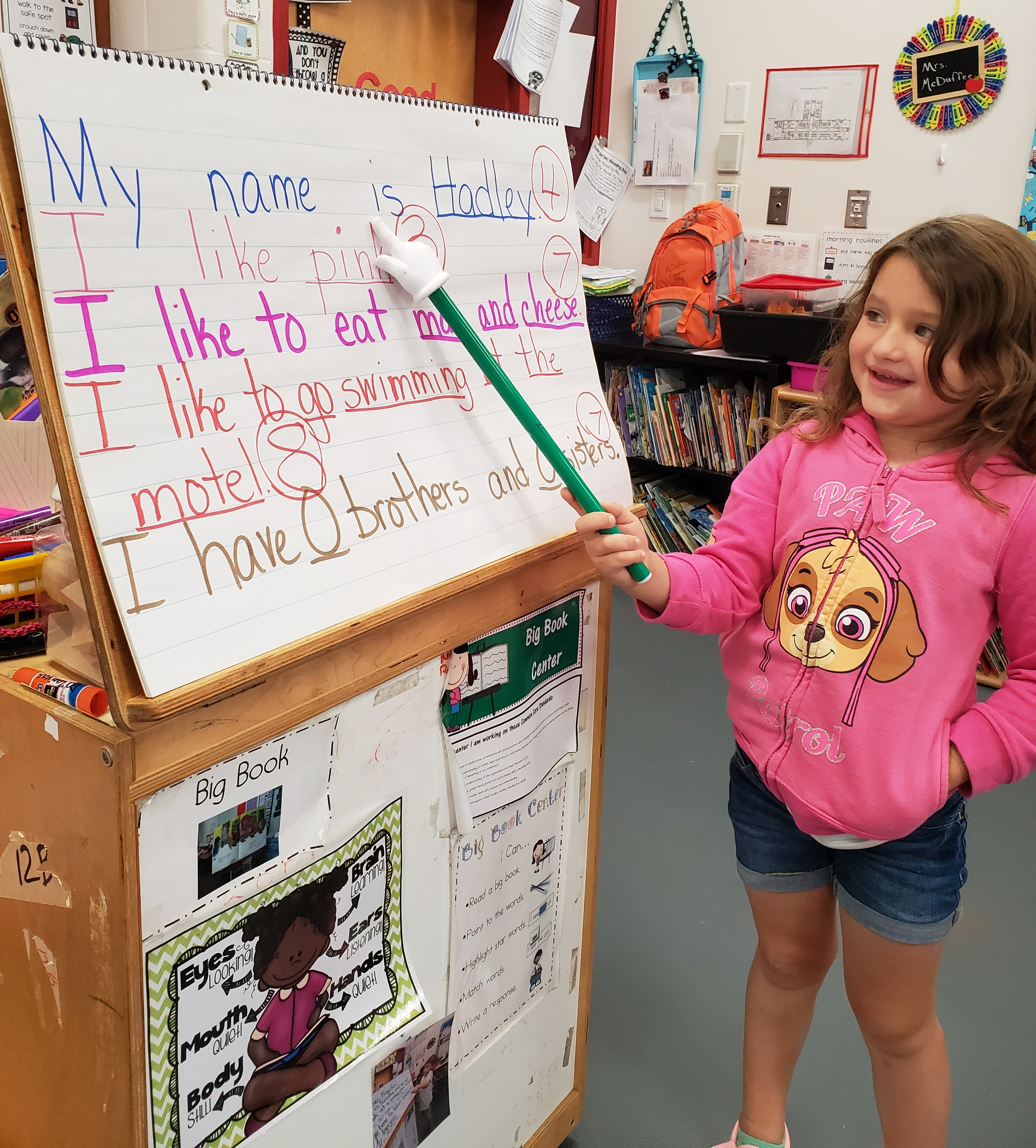 A girl presenting a set of sentences for the class and sharing facts about herself.