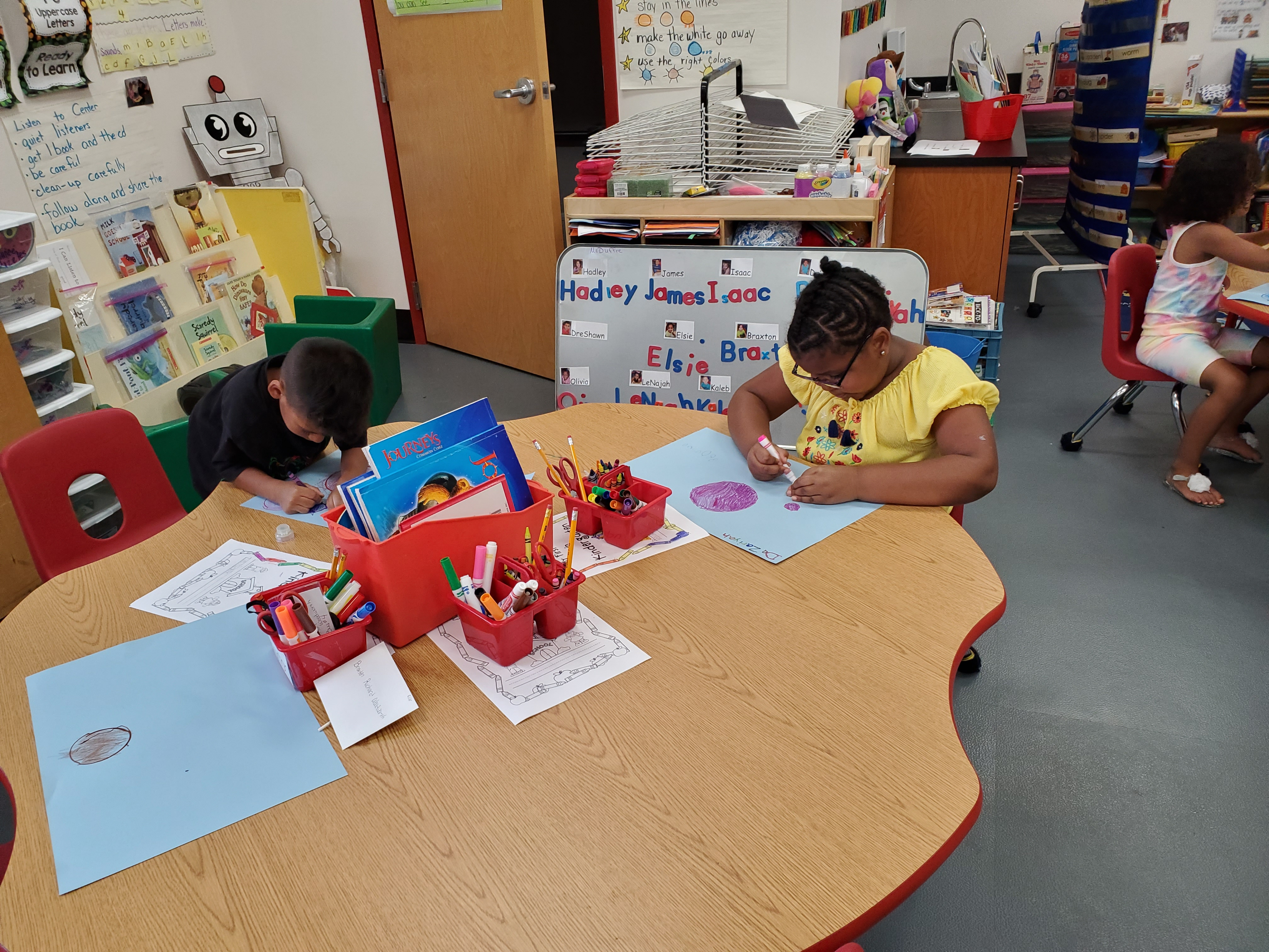 Two students sitting on a table drawing and painting circles on their own piece of paper.