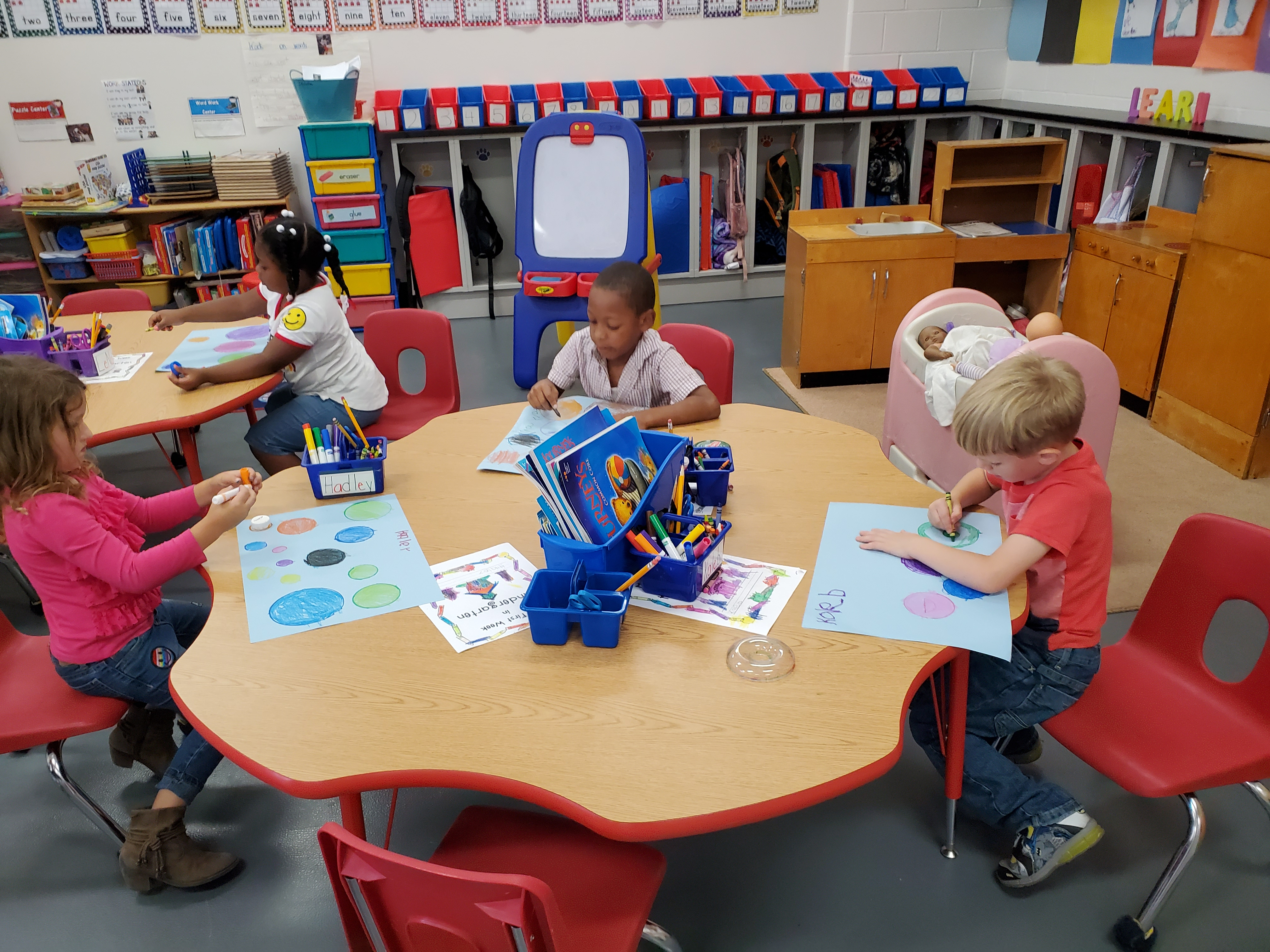 Three students sat around the table, drawing circles of very different colors.