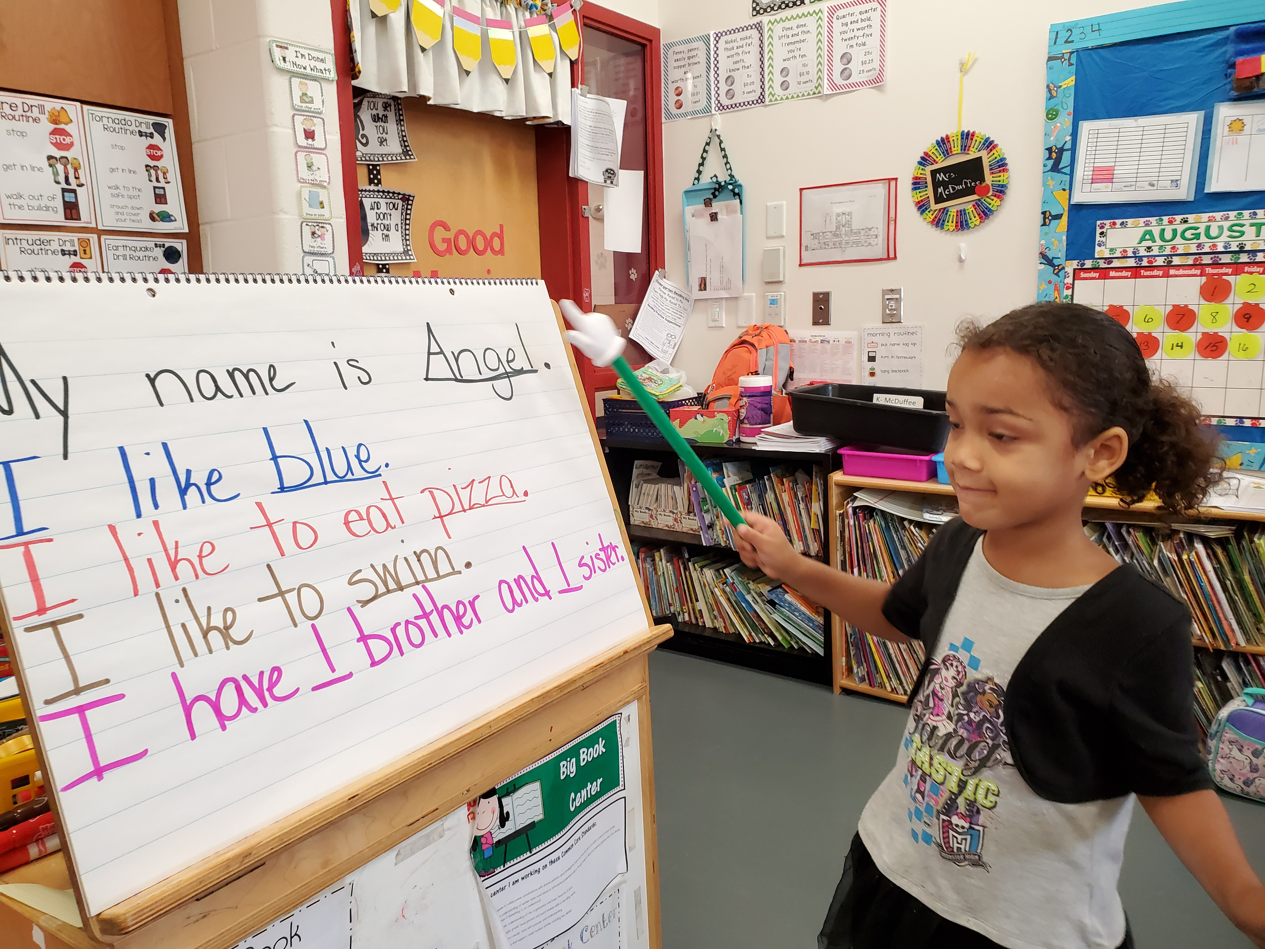 A girl presenting her own set of sentences in front of the class.