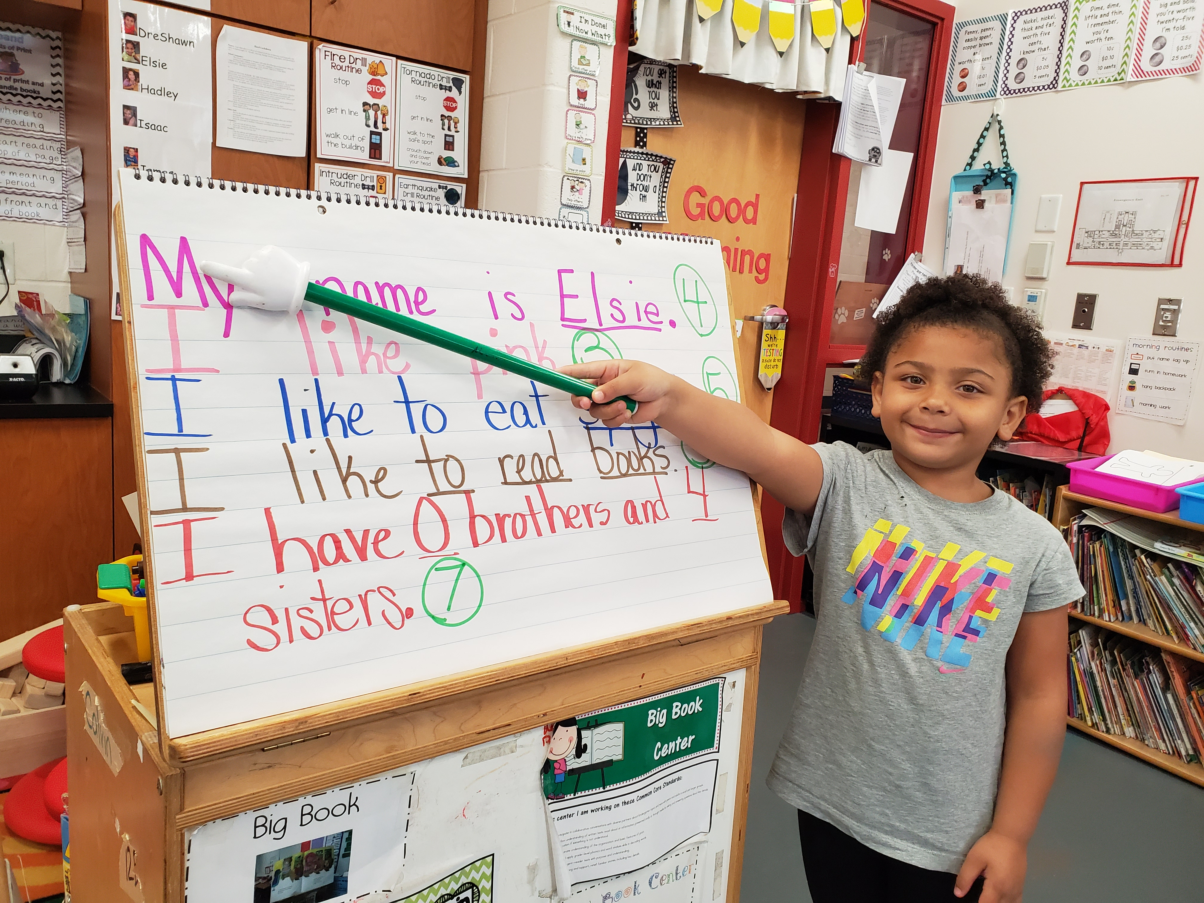 A girl presenting her own sentences to the rest of her classmates.