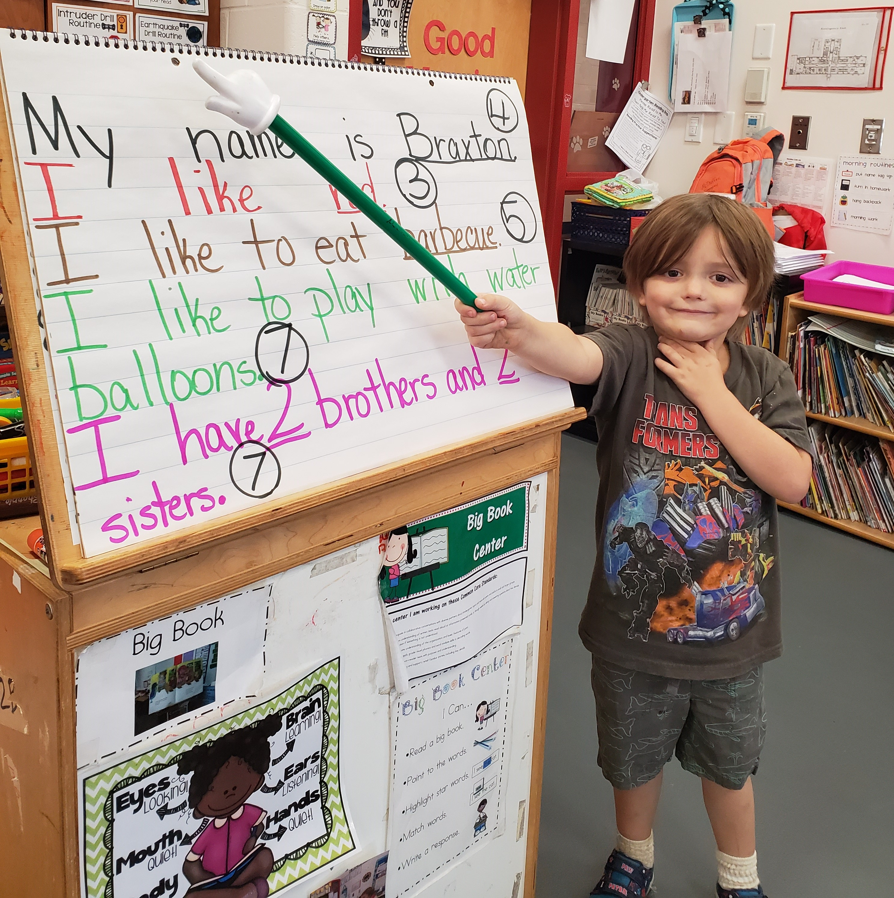 A boy presenting his sentences and telling the class about himself.