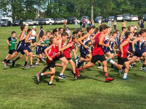A photo of all the students in the Cross Country club running around the field.