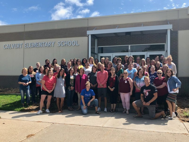 The whole school staff taking a photo in front of the Calvert Elementary School building.