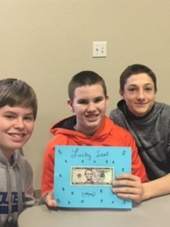 photo of middle schoolers holding up a $5 bill