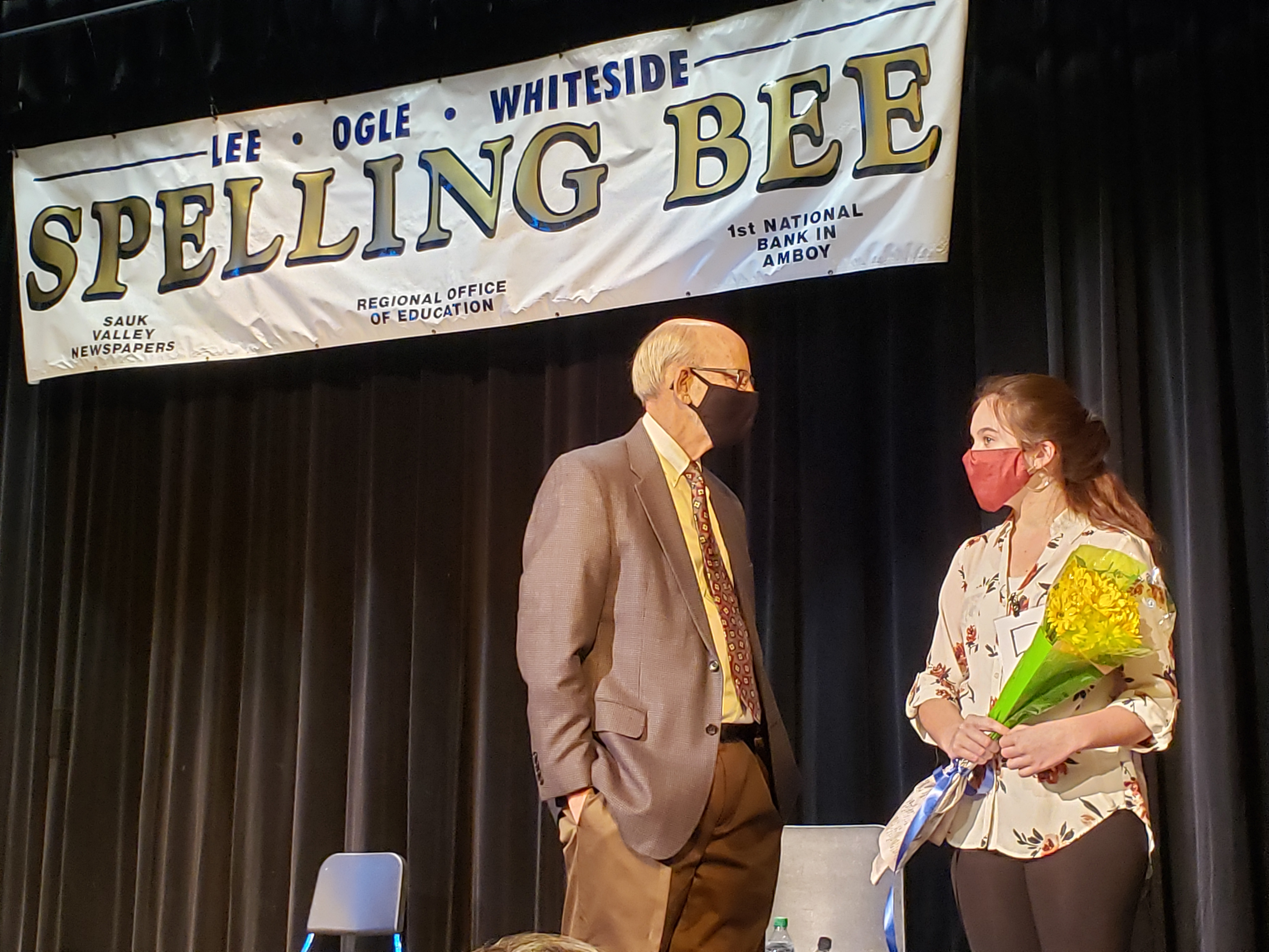 Photo of spelling bee winner with the moderator on stage