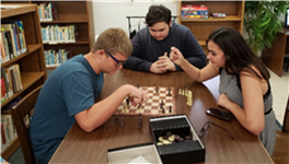 A group of students playing chess at the library