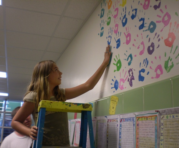Photo of students and teachers paiting their hand-prints on a wall