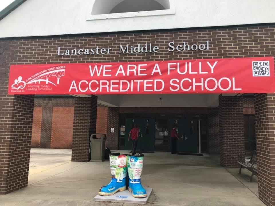 "picture of the front of Lancaster Middle School with a banner that reads ""we are a fully accredited school"""