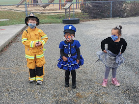 three students pose in costume