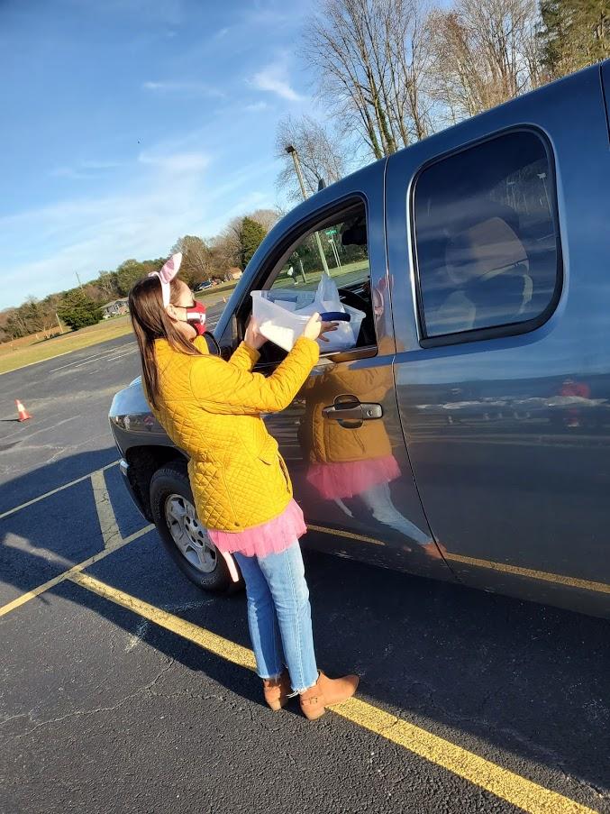 LPS teacher providing books to a family