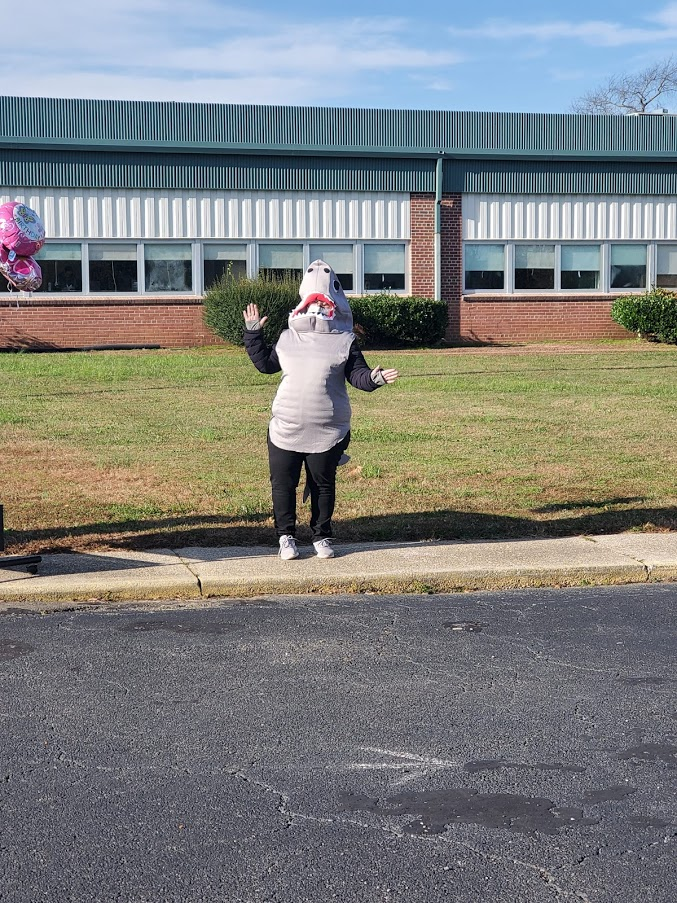 A teacher in costume waves to families