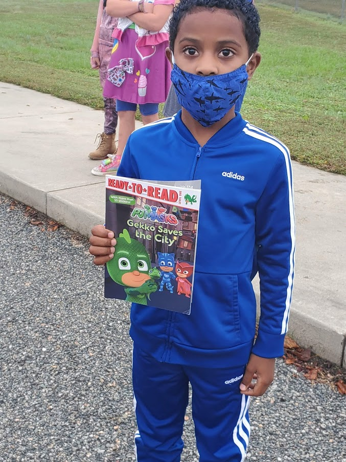 LPS student posing with his new book