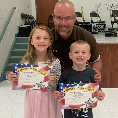 Principal poses with two smiling students receiving award