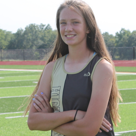 Student athlete poses in track uniform on football field