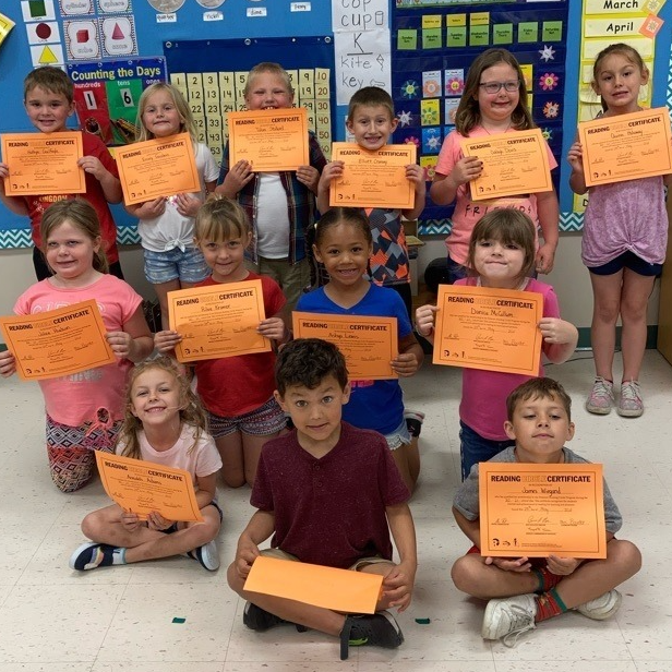 Elementary students hold certificates