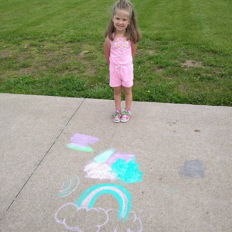 Young girl smiles with chalk art on playground