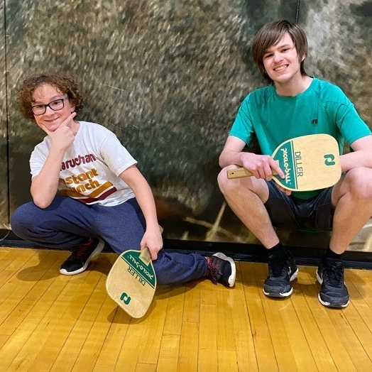 Two young men pose with ping-pong paddles in gym