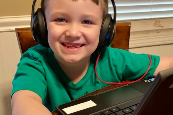 student wears headphones and works on Chromebook