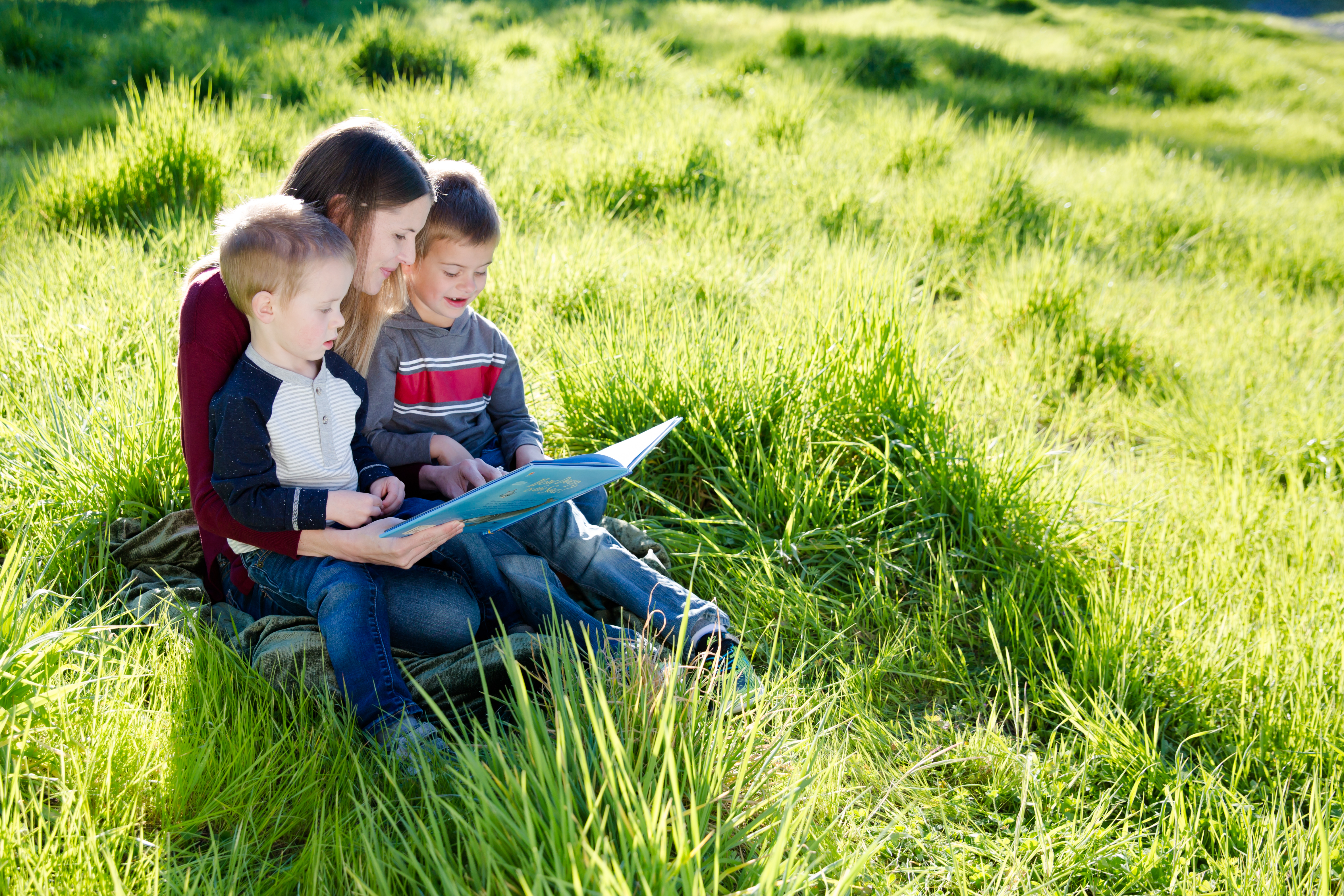 family reading in grass
