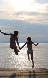 Photo of two girls jumping off the pier and into the ocean