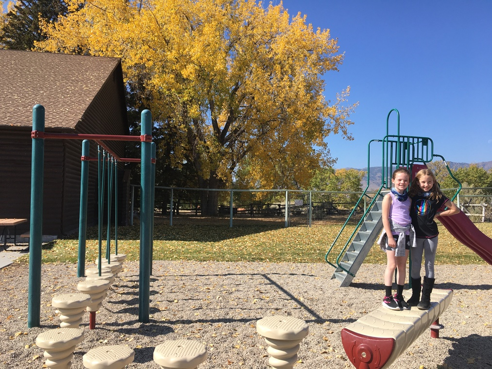 Two students on the playground outside Wapiti Elementary