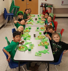Kids all lines up for their lunch and smiling at the camera