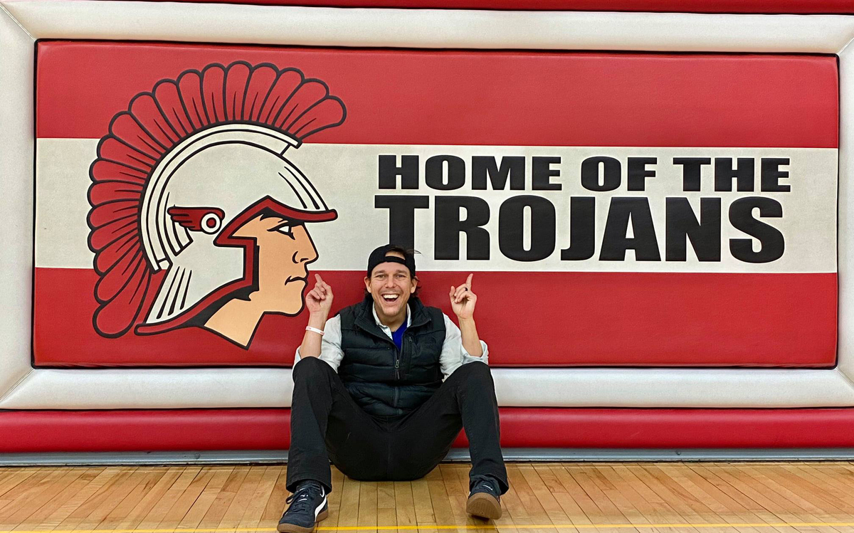 Joe Beckman posing in front of Home of the Trojans sign