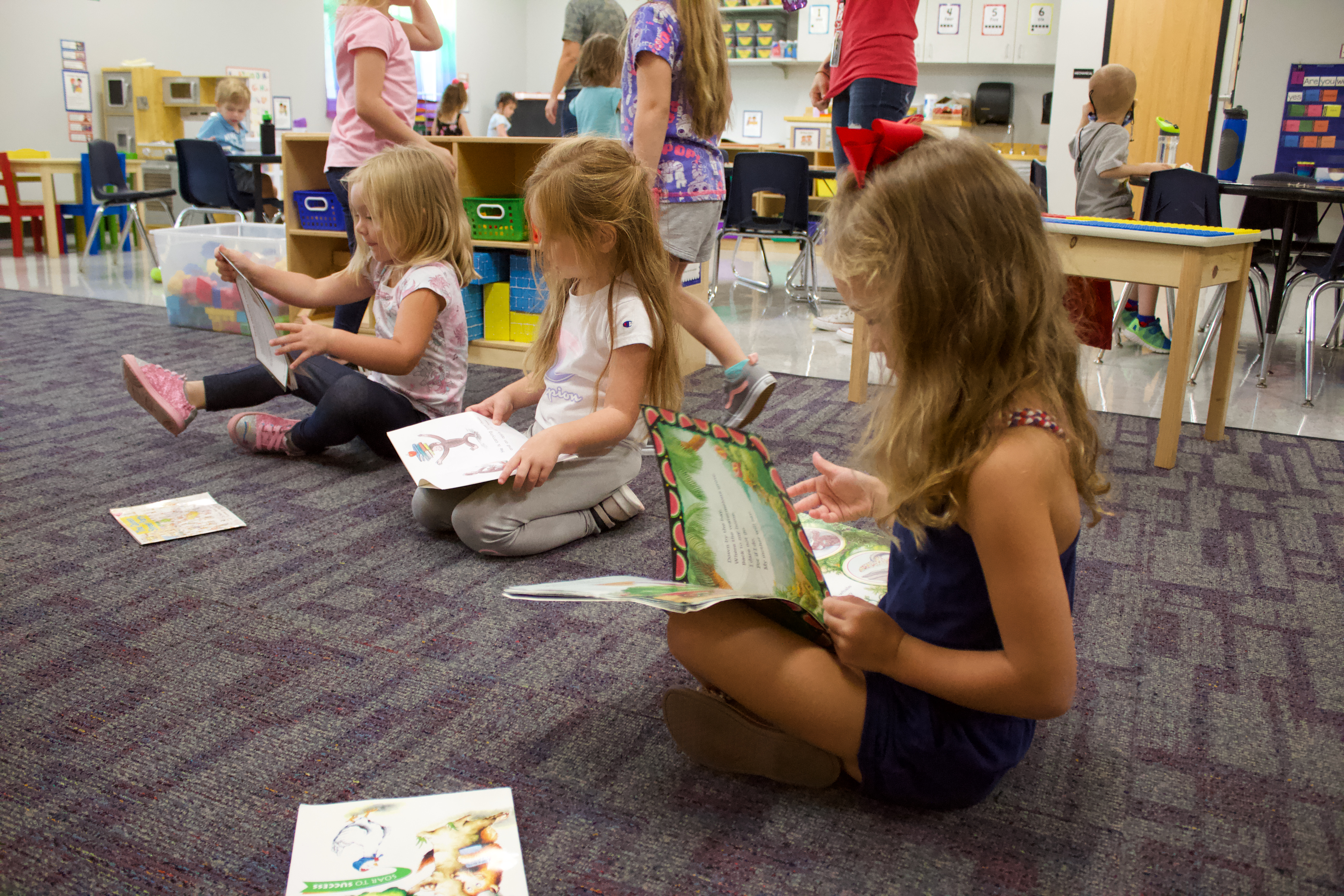 Preschool students sitting on the floor looking at picture books